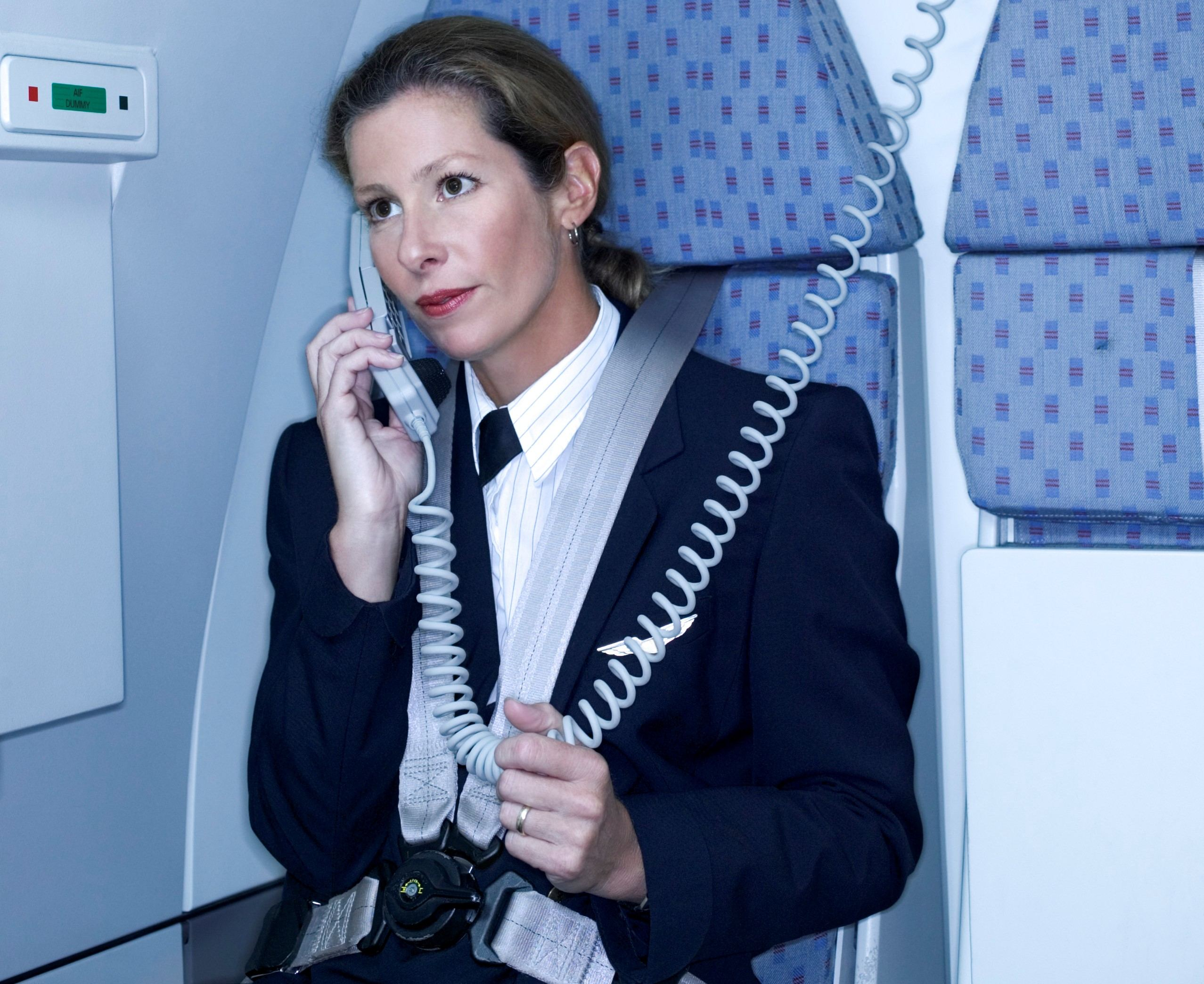Flight attendant using the phone on an airplane
