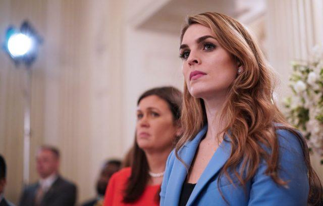 Hope Hicks listening to a speaker in a blue suit.