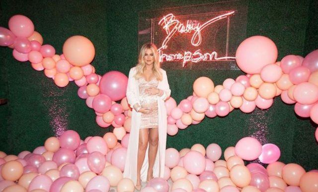 Khloé Kardashian pregnant surrounded by pink balloons.
