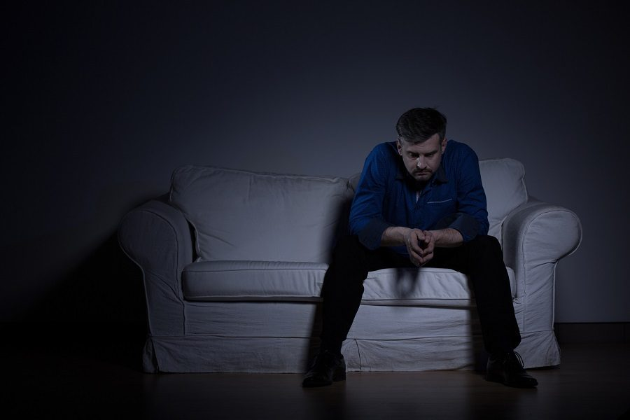 Hopeless man sitting on the sofa and thinking