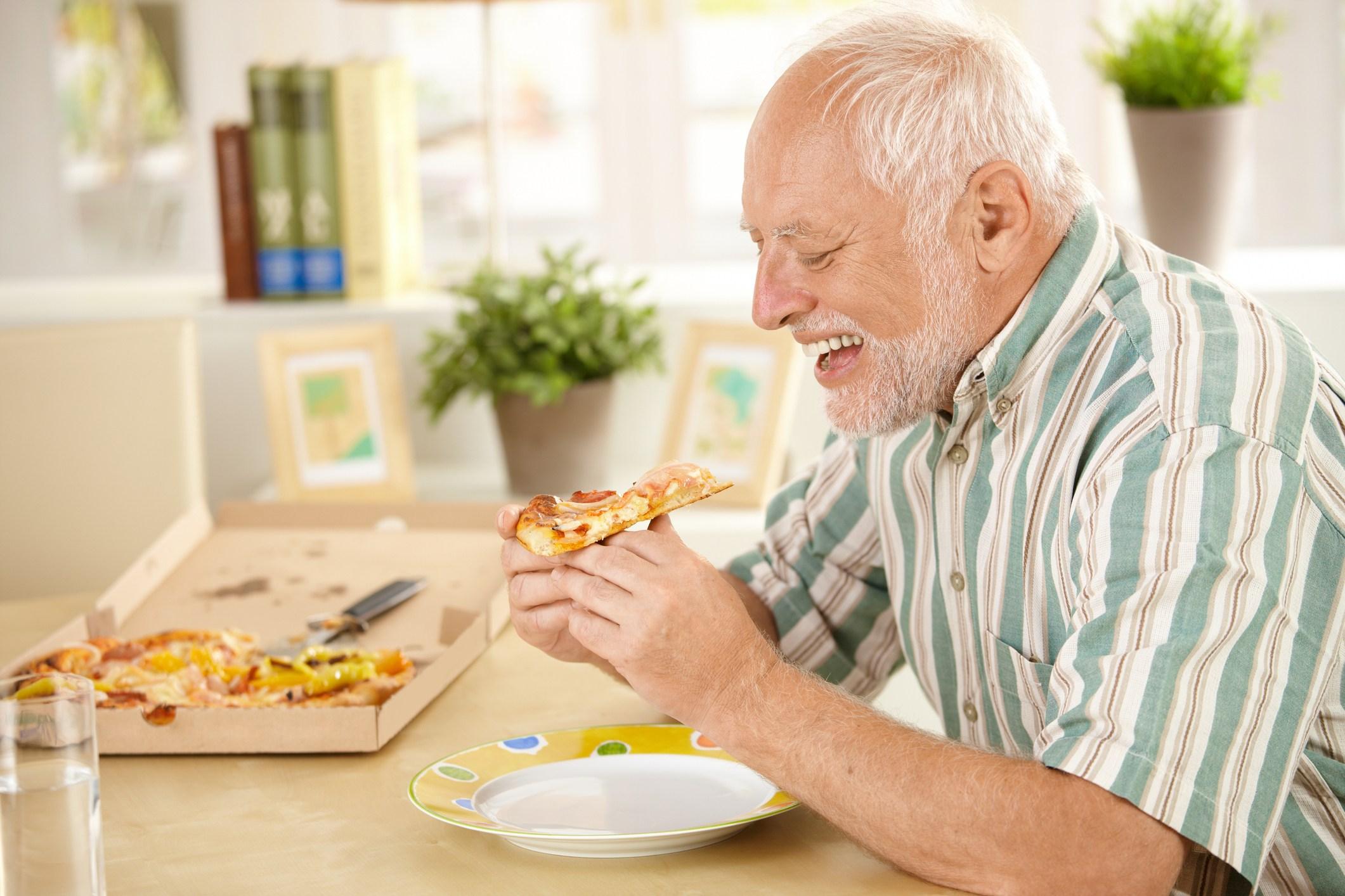 Smiling older man eating pizza