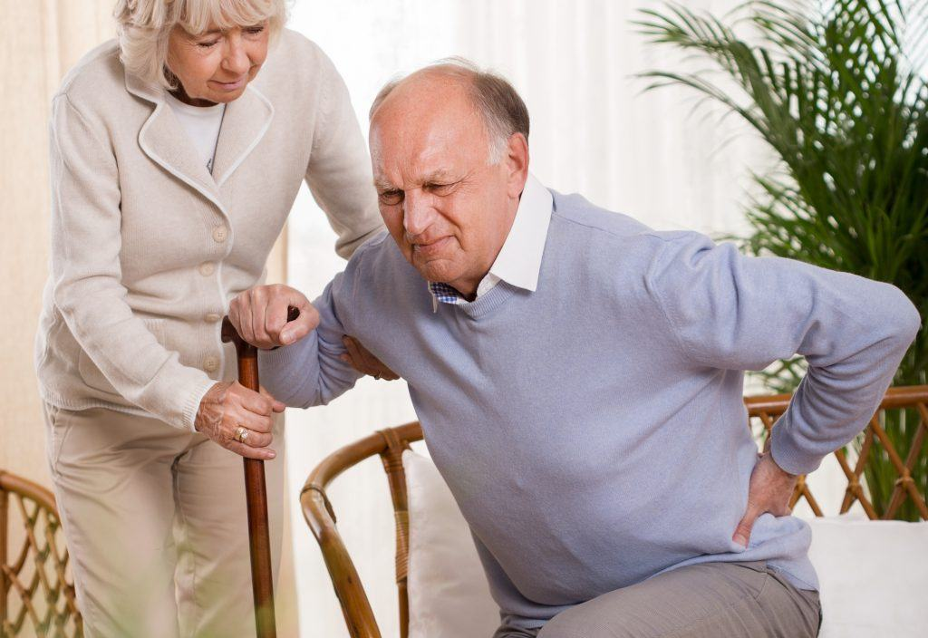 Senior man with pain in his back being helped by a woman