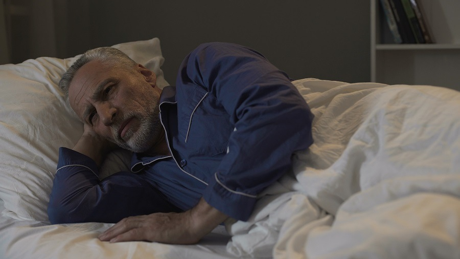 Elderly man in his bed
