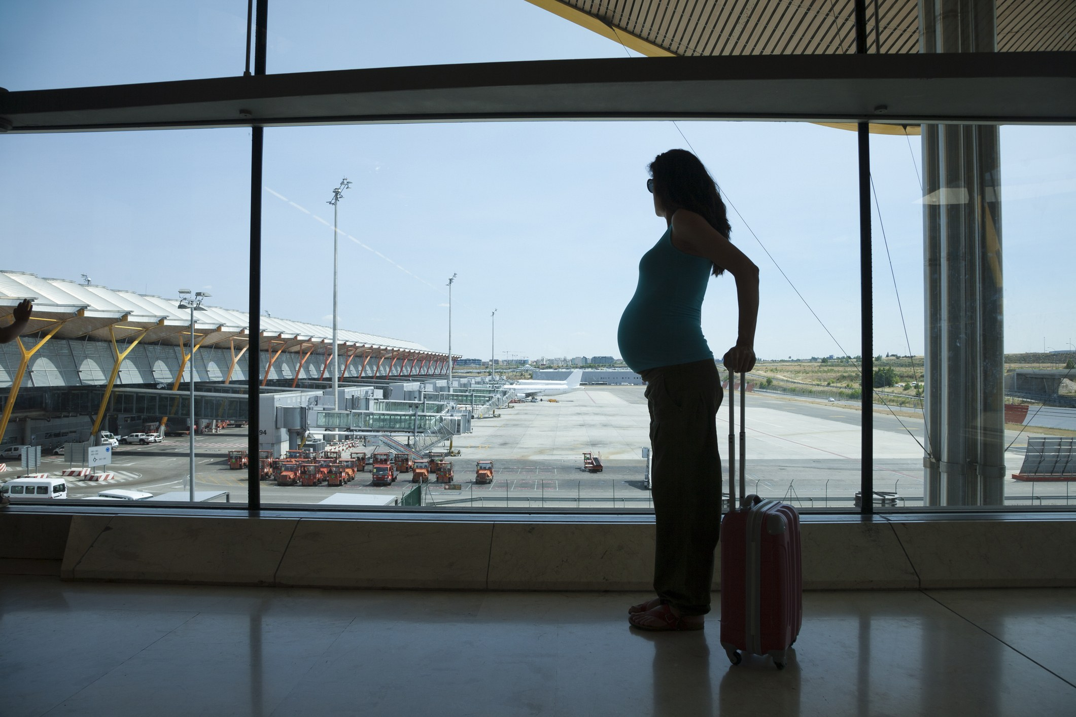 Silhouette of a pregnant woman waiting to fly in airport hall
