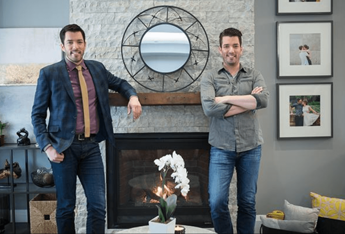 Property Brothers in front of a fireplace
