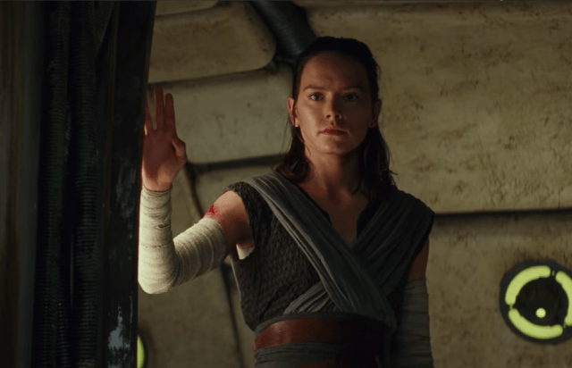 Rey standing next to a dark curtain.