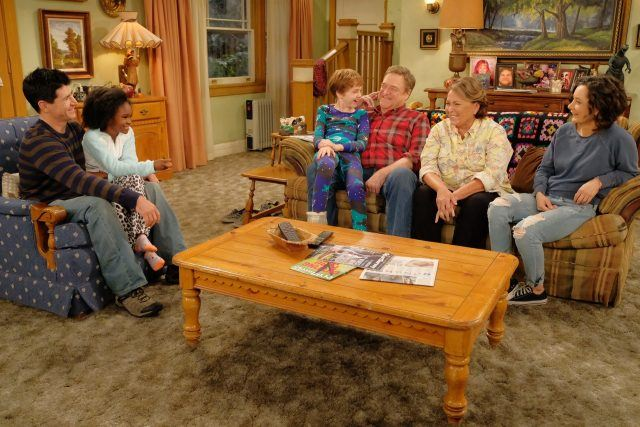 Roseanne sitting in the living room with her family.
