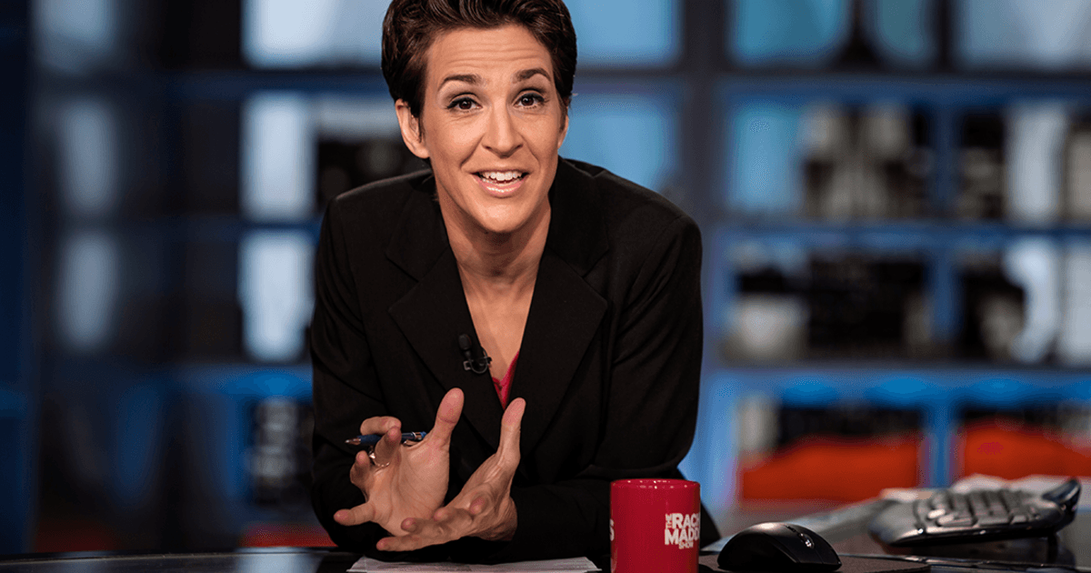 Rachel Maddow speaking and gesturing with her hands while being a news desk.