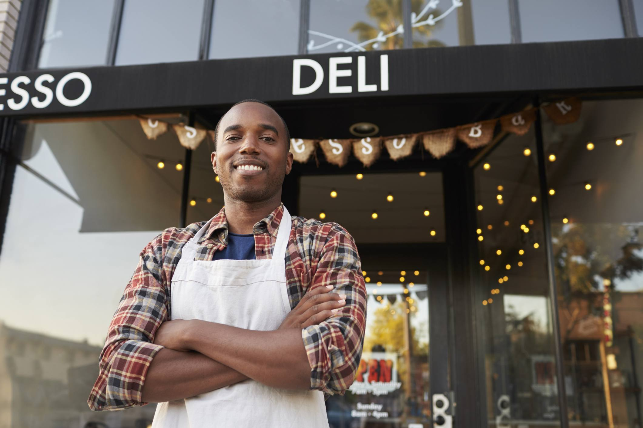 Black male small business owner standing outside coffee shop