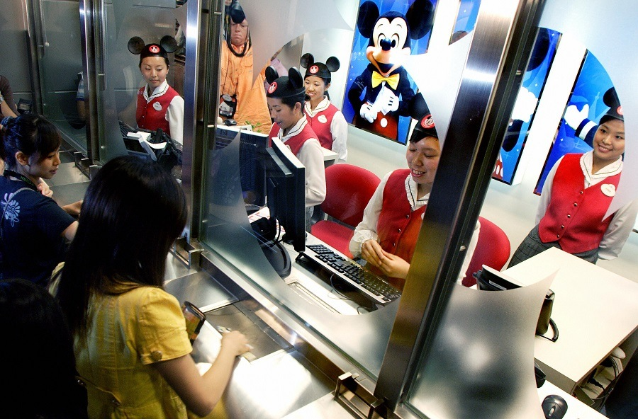 People buy the first tickets for the new Hong Kong Disneyland
