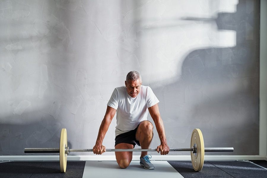 senior man in sportswear kneeling alone in a gym