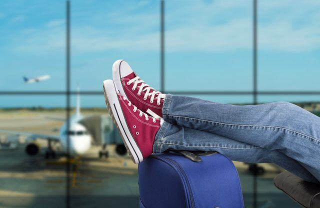 young man waiting for the plane at an airport
