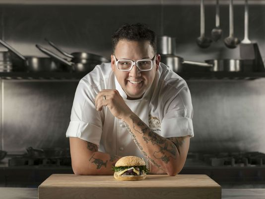 Graham Elliot poses above a burger