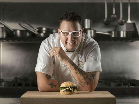 Graham Elliot poses above a burger