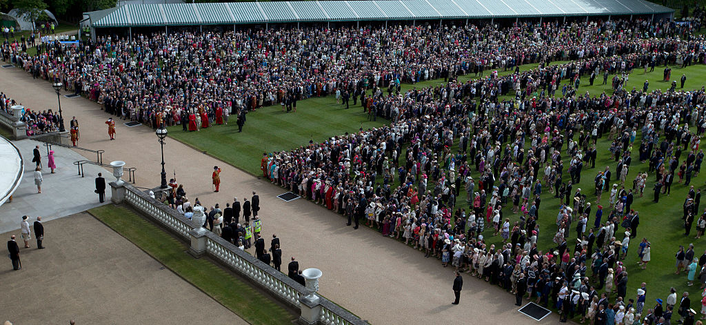 Queen Elizabeth II (wearing pink) stands with Prince Philip, Duke of Edinburgh on the top of the steps in front of members of the public