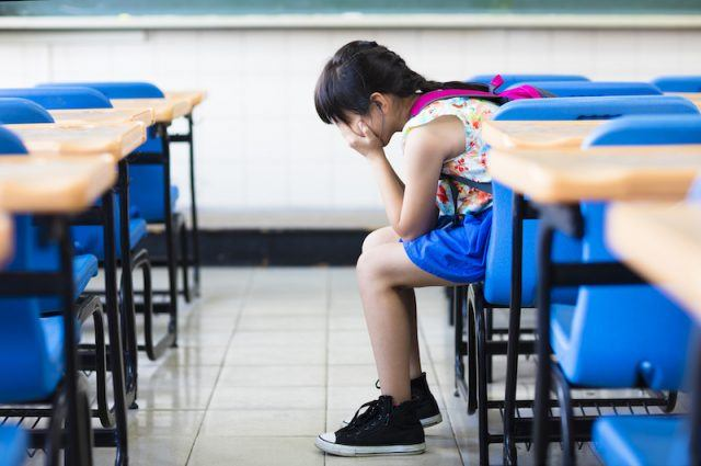 A young woman sitting sadly in a classroom.