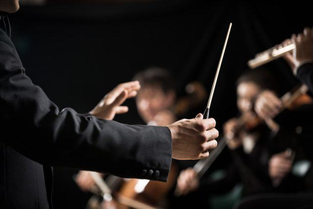 A conductor in front of an orchestra.