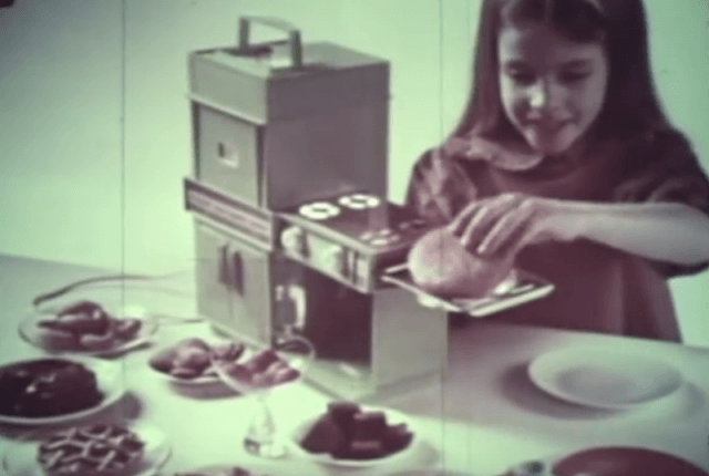 A young girl plays with an Easy Bake Oven.
