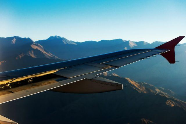 An airplane flying past a mountain range.