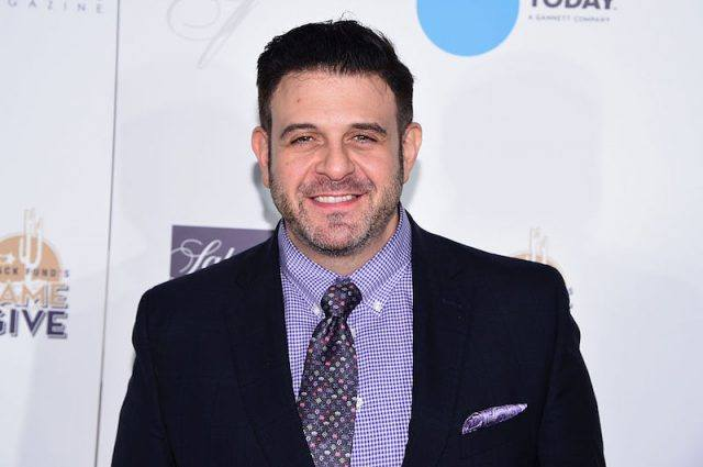 Adam Richman smiling on a red carpet.