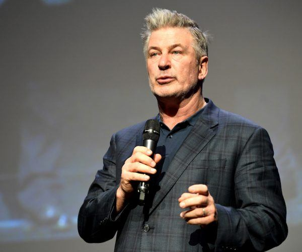 Alec Baldwin holding a microphone and speaking on stage.
