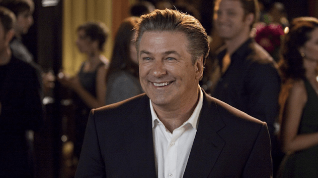 Alec Baldwin smiling while in a suit in 'It's Complicated'.