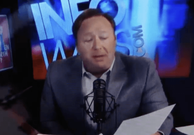 Alex Jones reading off a piece of paper into a microphone.