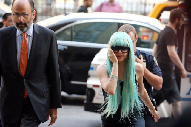 Amanda Bynes wearing a blue wig while entering a court room.