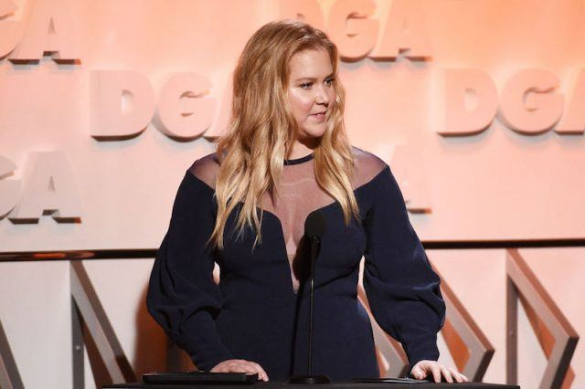 Amy Schumer speaking at a podium on stage.