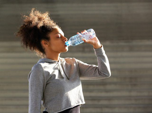 An athletic woman drinks water from a plastic bottle.
