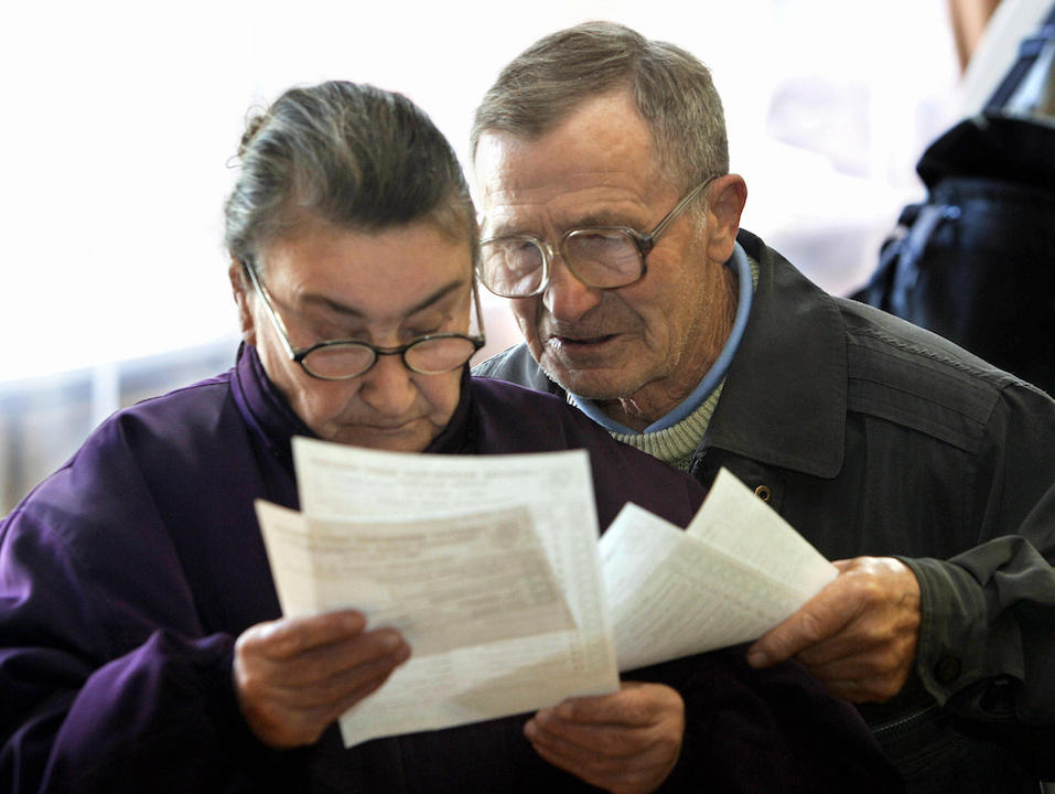 An elderly couple looking at paper work
