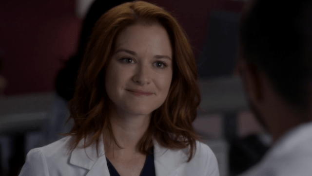 April wearing a white coat and speaking to a man across a table on 'Grey's Anatomy'.