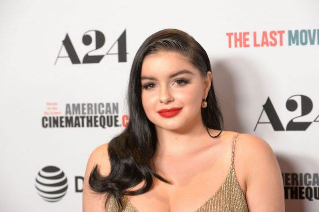 Ariel Winter wearing red lipstick and a gold dress on a red carpet.