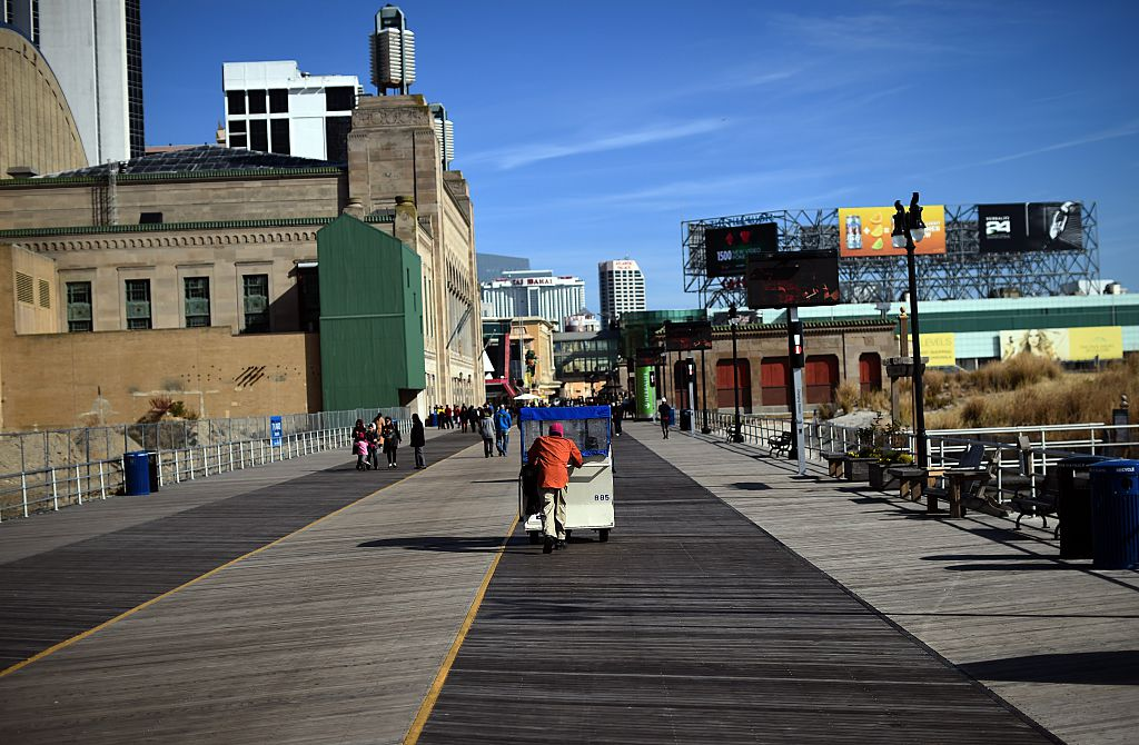 "A man moves passengers on a ""push cab"" along the boardwalk in Atlantic City."