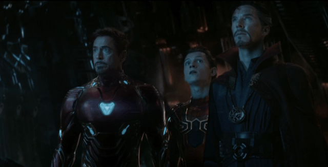 Tony Stark standing with other characters in a dark room.