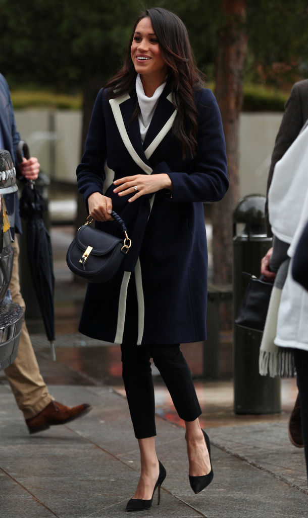 Britain's Prince Harry's fiancee US actress Meghan Markle greets well-wishers as she arrives with the prince at Millennium Point to attend an event
