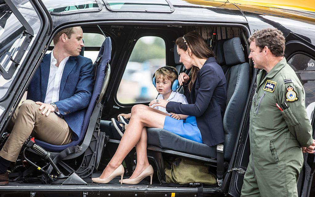 Britain's Prince George sits in a 'Squirrel' helicopter with his mother Catherine, Duchess of Cambridge and father Prince William during a visit to the Royal International Air Tattoo at RAF Fairford