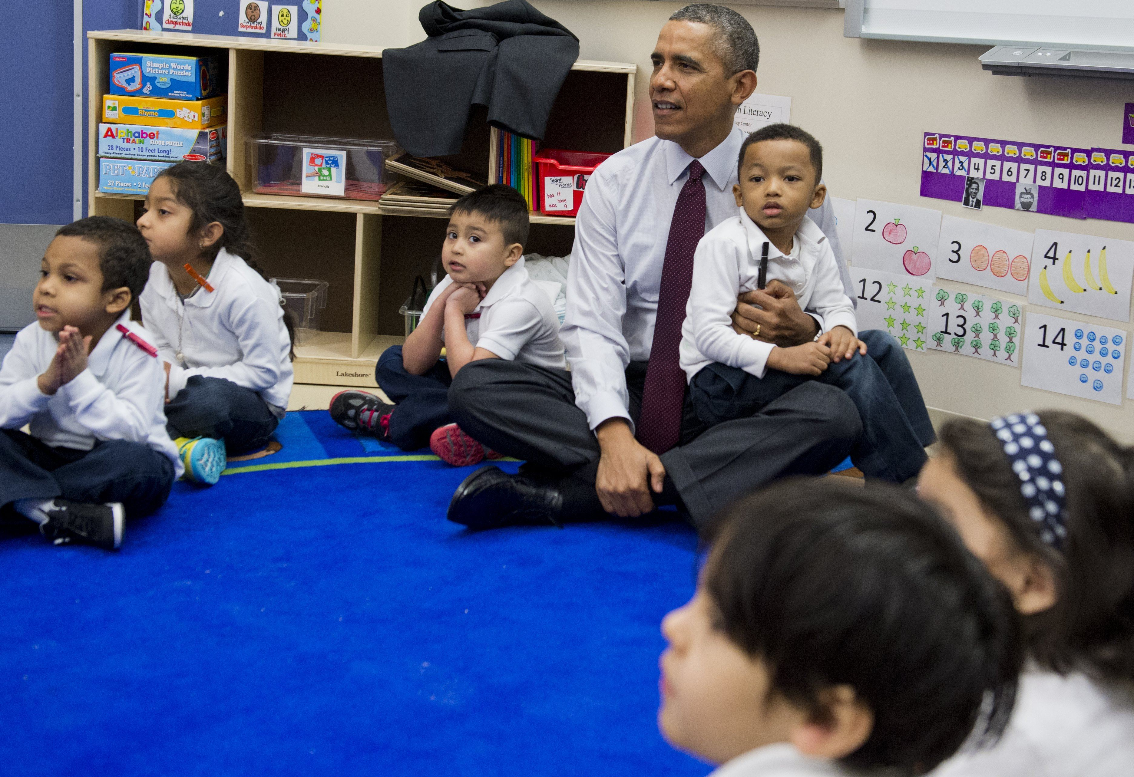 Barack Obama sits cross legged on the floor and holds a child in his lap