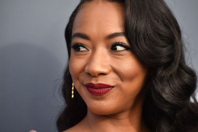 Betty Gabriel smiles as she poses on a red carpet.