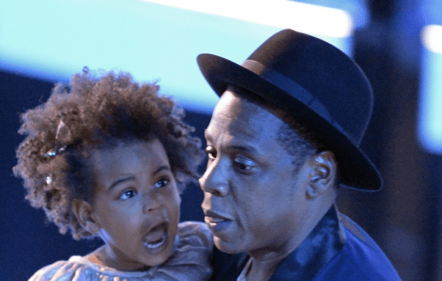 Jay-Z holding Blue Ivy on stage.
