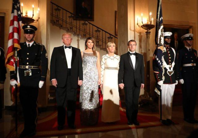 President Donald Trump and First Lady Melania Trump stand with French President Emmanuel Macron and his wife, Brigitte Macron at the start of a State Dinner in the White House.