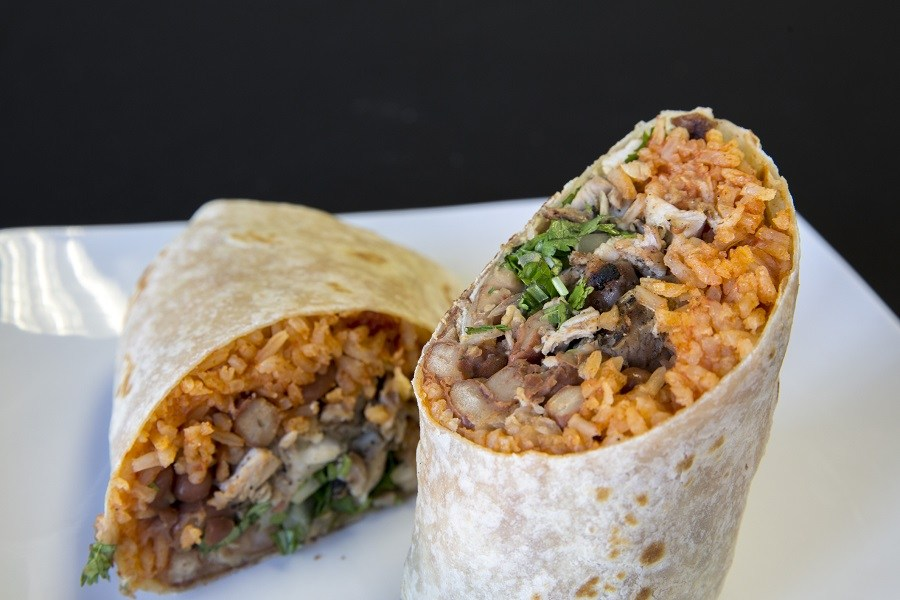 Tow halves of a burrito with rice, beans, and steak on a white plate