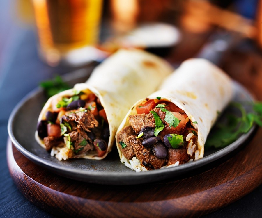 two mexican steak burritos with beer