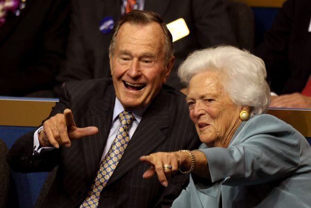 George H.W. Bush and Barbara Bush pointing together.