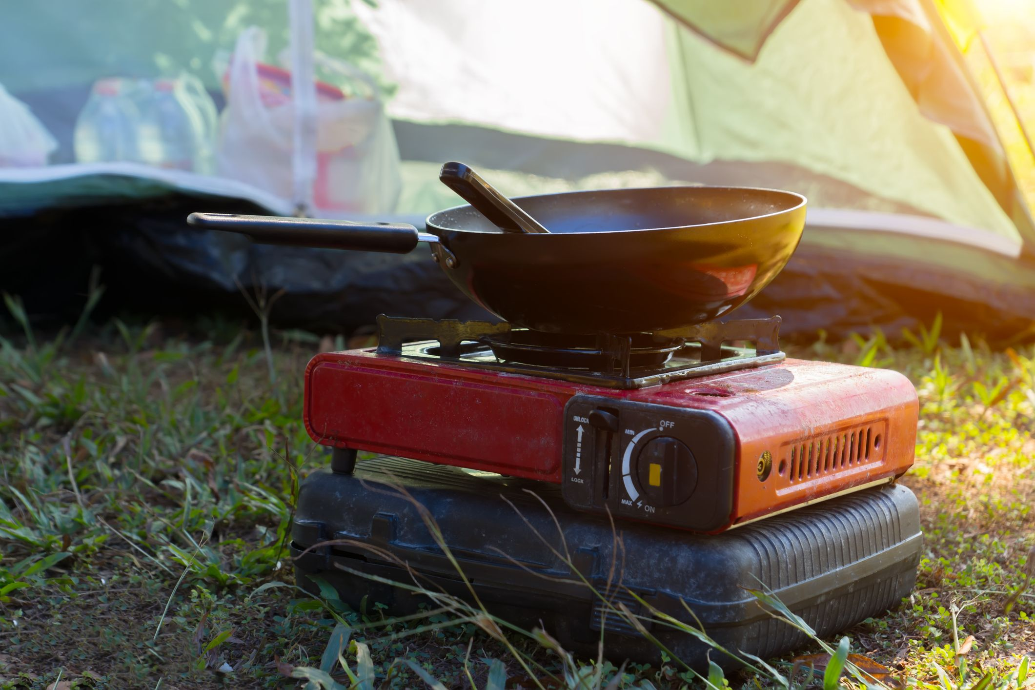 Portable gas stove and a frying pan in the camp with sunlight.