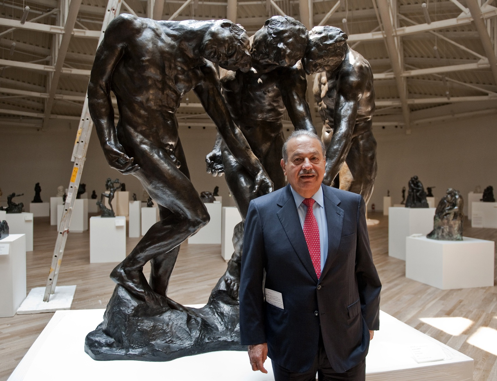 Mexican tycoon Carlos Slim poses next to a statue