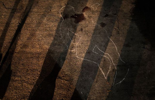 A chalk outline remains on a street in Manila after the funeral personnel