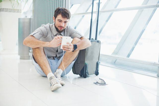 man waiting for his flight at the airport and speaking on his phone