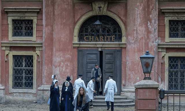 A group of people standing in front of the Charité.