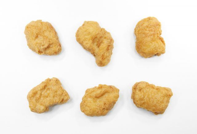 Six chicken nuggets on a white table.